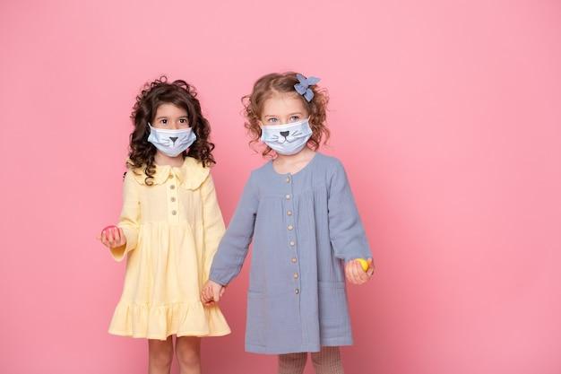 Twee meisjes in beschermend masker met gekleurde eieren hand in hand. covid pasen-concept.