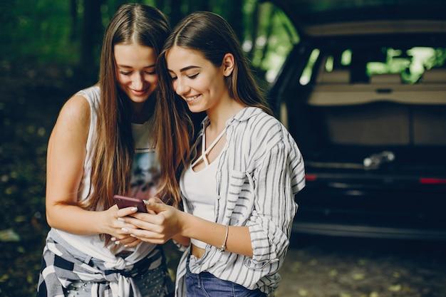 Twee meisjes in de buurt van de auto