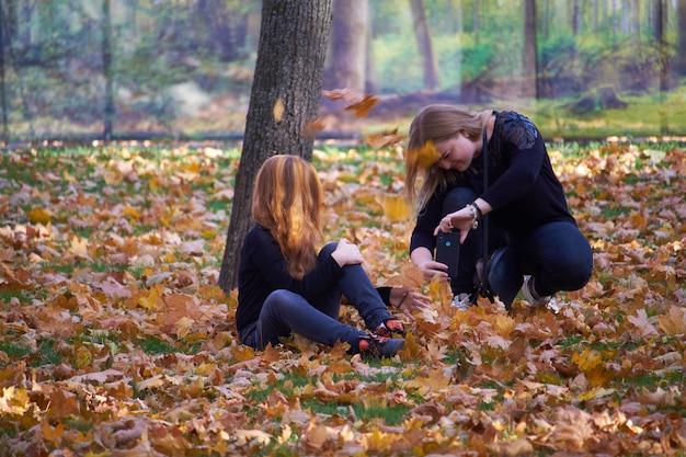 Twee meisjes in de herfstpark nemen een selfie, selectieve nadruk