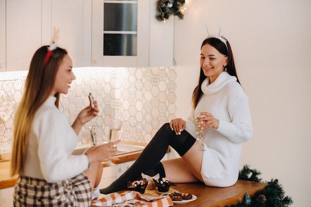 Twee meisjes in een gezellige huiselijke omgeving in de keuken met champagne in hun handen voor kerstmis. lachende meisjes drinken champagne op een feestelijke avond