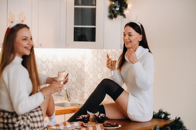 Twee meisjes in een gezellige huiselijke omgeving in de keuken met champagne in hun handen voor kerstmis. lachende meisjes drinken champagne op een feestelijke avond.