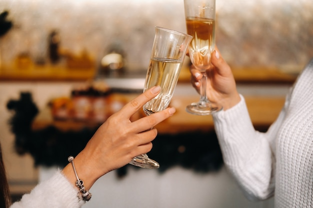 Twee meisjes in een gezellige huiselijke omgeving met champagne in hun handen met kerstmis. lachende meisjes drinken champagne op een feestelijke avond