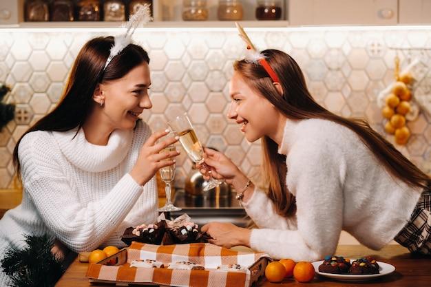 Twee meisjes in een gezellige huiselijke omgeving met champagne in hun handen met kerstmis. lachende meisjes drinken champagne op een feestelijke avond.