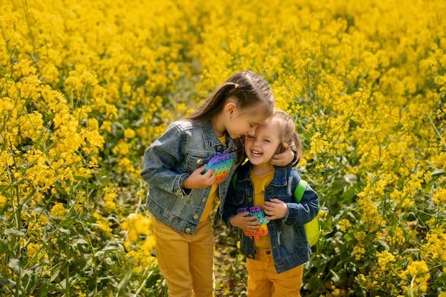 Twee meisjes in een koolzaadveld omhelzen elkaar teder en lachen terwijl ze een populair popit-speeltje vasthouden