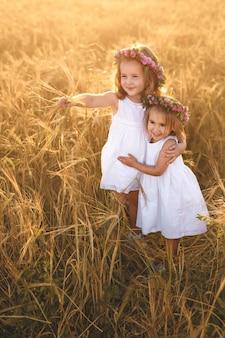 Twee meisjes in een tarweveld, een van hen wees in de verte.