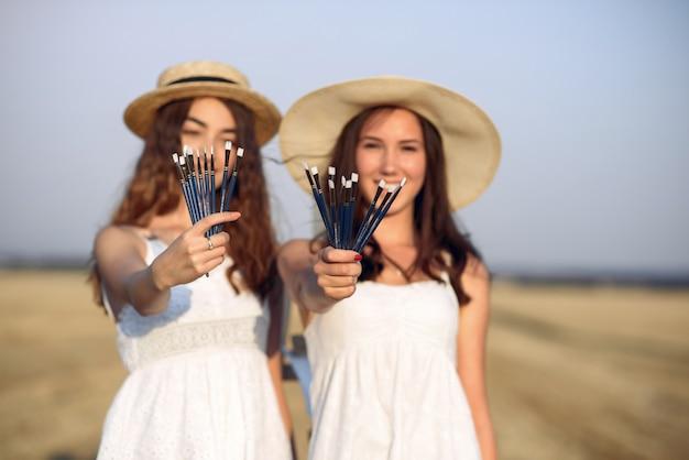 Twee meisjes in een witte jurk schilderij in een veld