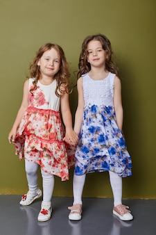 Twee meisjes in felle lentekleren op een olijfkleurige achtergrond