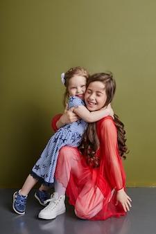 Twee meisjes in heldere lente kleren knuffelen