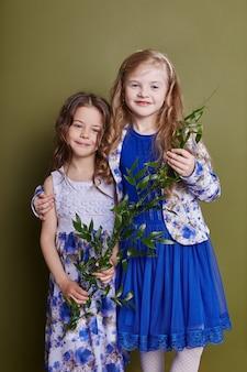 Twee meisjes in heldere lentekleren op een olijfkleurige achtergrond