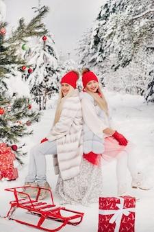 Twee meisjes in het winterbos in de buurt van een versierde kerstboom.