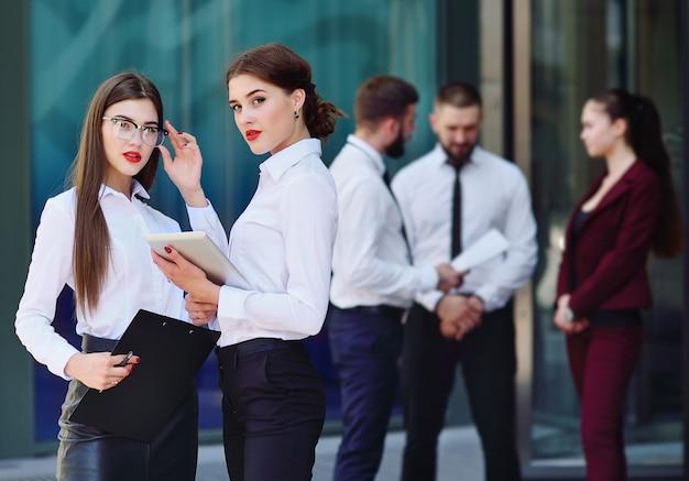 Twee meisjes in office-stijlkleren bij de bouw van achtergrond