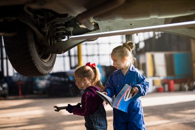 Twee meisjes in overall staan met roet en magazine