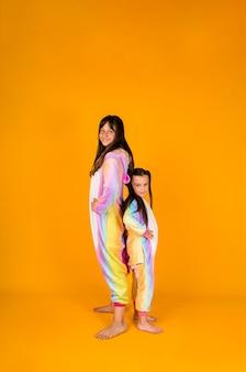 Twee meisjes in pluche pyjama's staan op een gele achtergrond met een plek voor tekst
