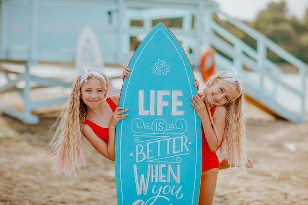 Twee meisjes in rode zwemkleding poseren op het strand met blauwe surfplank