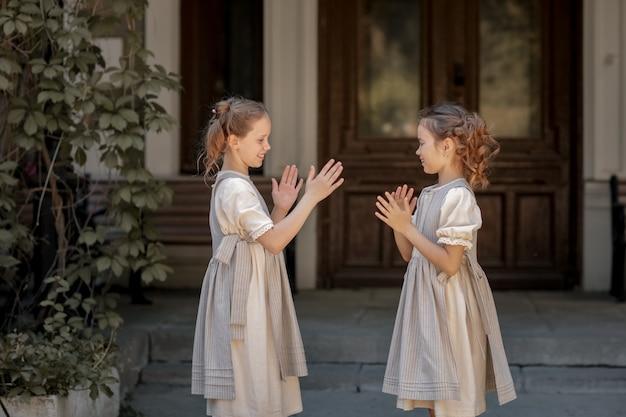 Twee meisjes in schoolkleding vermaken zich en spelen op straat tijdens de verandering.