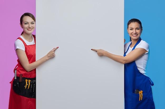 Twee meisjes in schorten poseren met een wit reclamebord. reclame concept