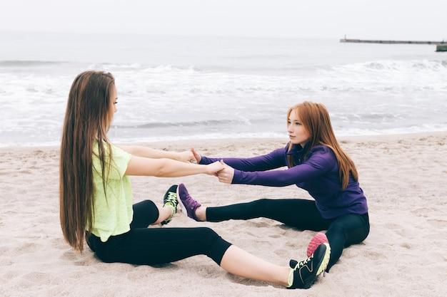 Twee meisjes in sportkleding doen die zich op een strand uitrekken