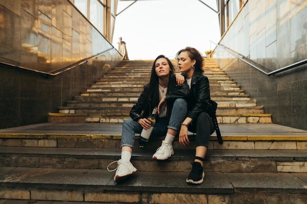 Twee meisjes in stijlvolle vrijetijdskleding zitten op de trap bij de uitgang van de metro