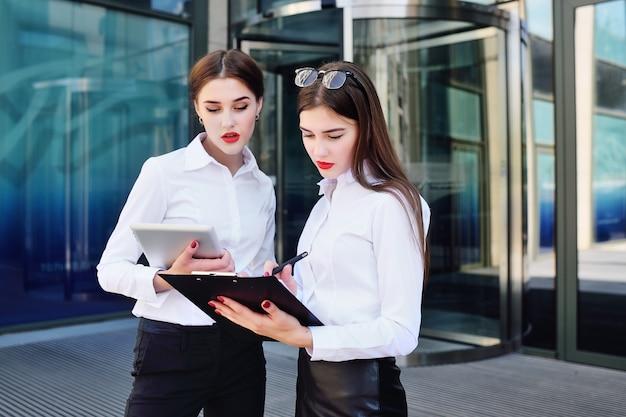 Twee meisjes in zakelijke kleding op de achtergrond van een kantoorgebouw