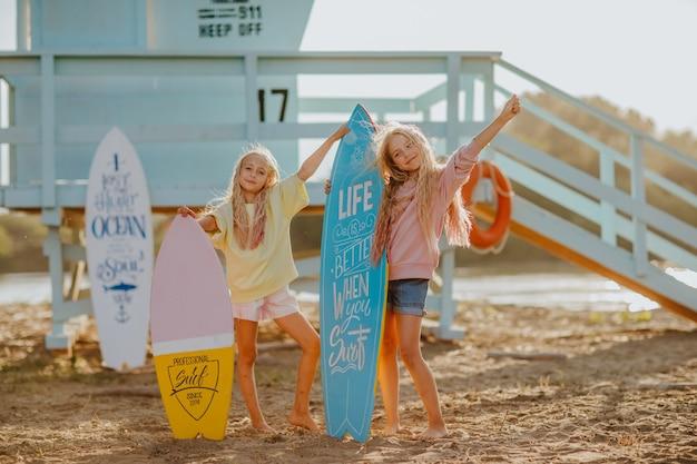 Twee meisjes in zomerkleren poseren met surfplanken tegen badmeestertoren op het strand