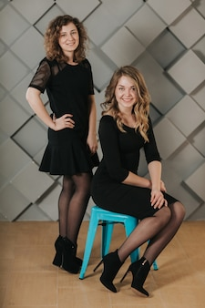 Twee meisjes in zwarte jurken met een blauwe stoel poseren