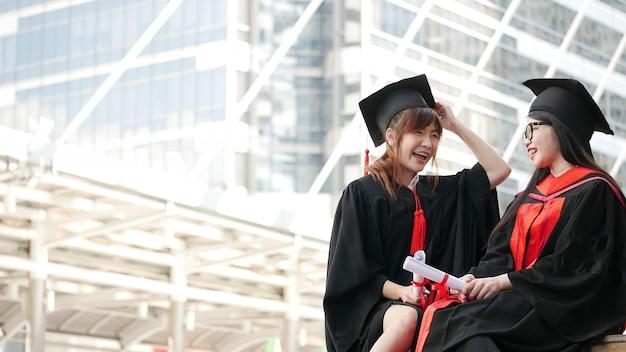 Twee meisjes in zwarte toga's en houden diploma-certificaat zitten en lachend met gelukkig afgestudeerd.