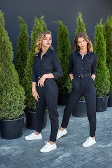 Twee meisjes in zwarte trainingspakken poseren in de buurt van thuja