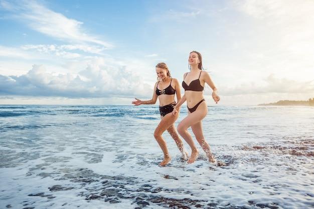 Twee meisjes in zwemkleding rennen langs het strand