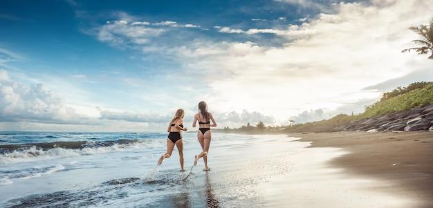Twee meisjes in zwemkleding rennen op het strand banner panorama