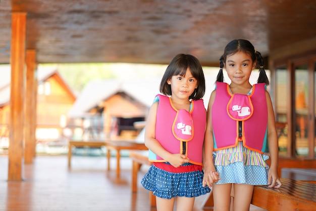 Twee meisjes in zwempak en reddingsvest houden hand samen