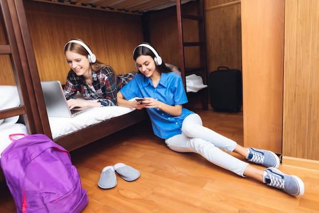 Twee meisjes kijken film op laptop op bed.