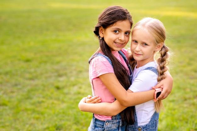 Twee meisjes knuffelen elkaar in een park
