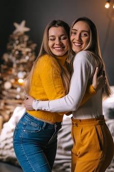 Twee meisjes knuffelen in kerstbinnenland