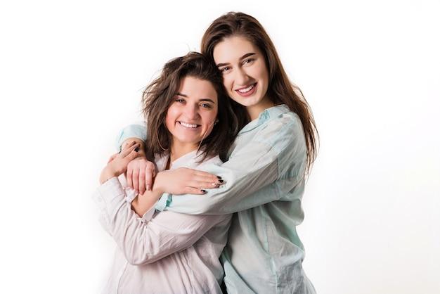Twee meisjes knuffelen op een witte achtergrond