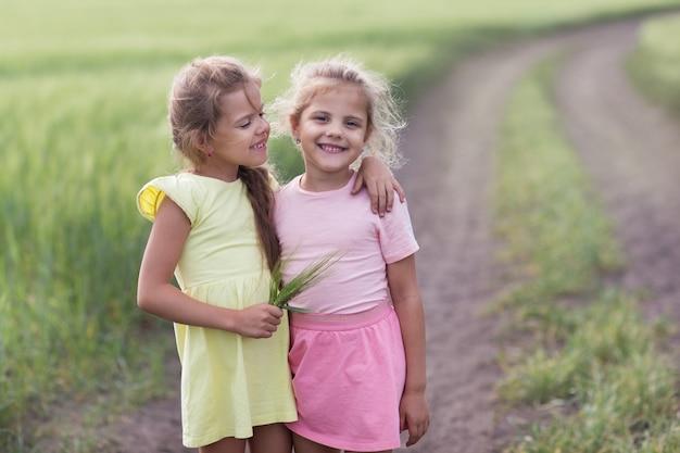 Twee meisjes knuffelen op het veld en de een kijkt naar de ander