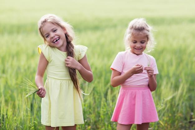 Twee meisjes lachen op een groen veld