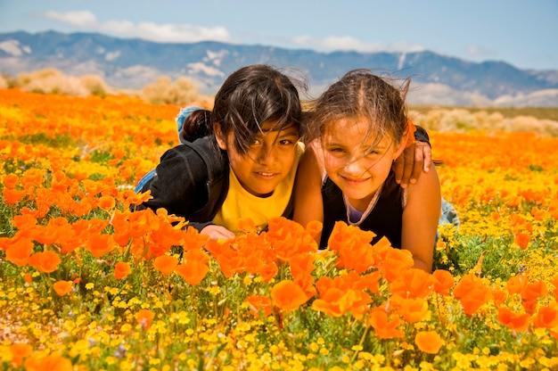 Twee meisjes leggen in poppy field