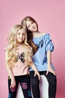 Twee meisjes lichte zomer ziet er prachtig uit kleding. bloemen op kop. meisjes hebben plezier en knuffelen