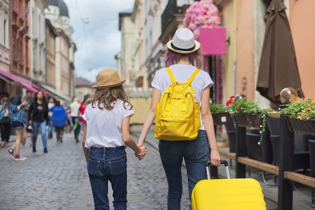 Twee meisjes lopen in de stad met koffer, achteraanzicht