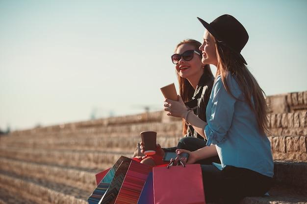 Twee meisjes lopen met boodschappentassen op de straten van de stad op zonnige dag