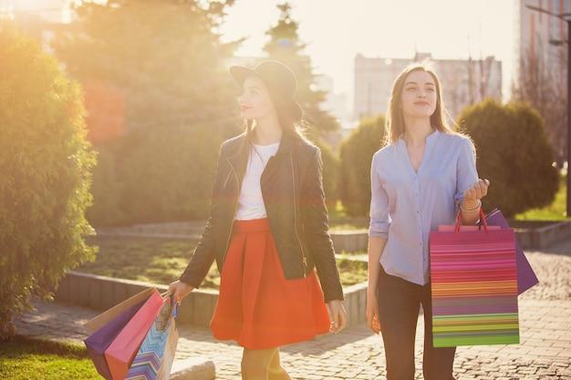 Twee meisjes lopen met winkelen in de straten van de stad