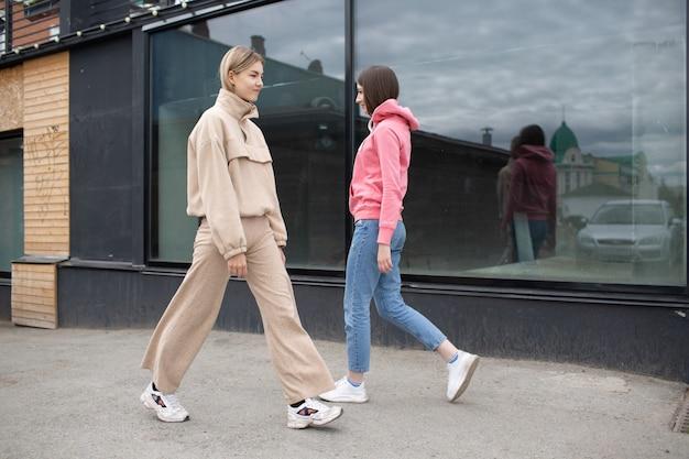 Twee meisjes lopen op de straat van de stad. jonge vrouw buitenshuis.