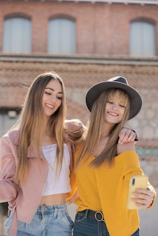 Twee meisjes maken een foto met een mobiel op straat