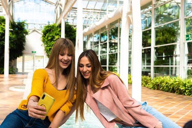 Twee meisjes maken een foto van zichzelf met hun mobiele telefoons zittend op een fontein