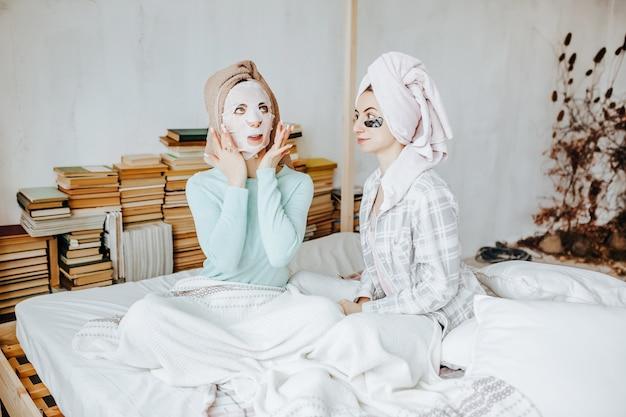Twee meisjes maken maskers en patches voor de schoonheid van gezicht en haar