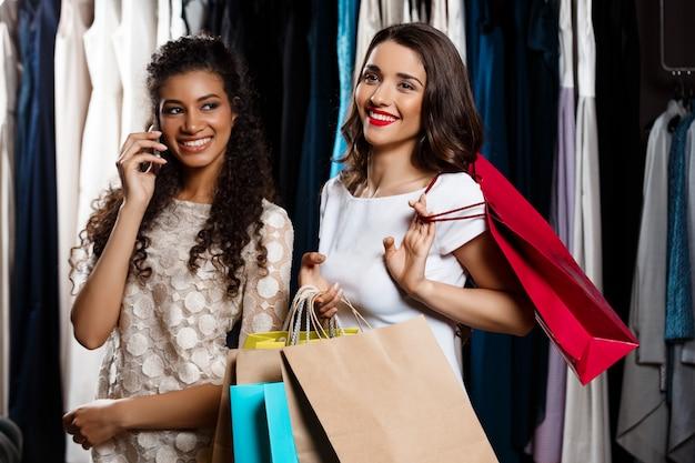 Twee meisjes maken winkelen in winkelcentrum. een die telefoneert.