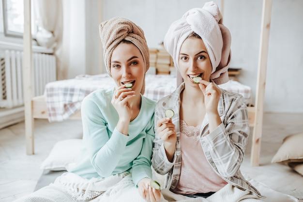 Twee meisjes maken zelfgemaakte gezichtsmaskers en haarmaskers met komkommers