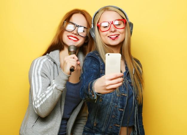 Twee meisjes met een microfoon zingen en plezier samen tijdens het maken van selfie