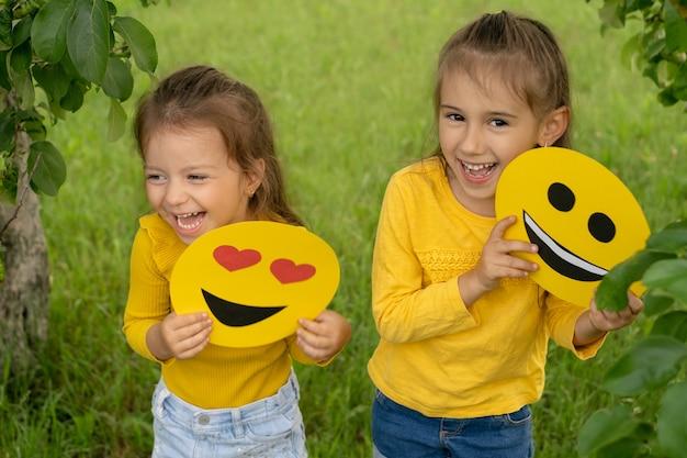 Twee meisjes met emoticons met blije gezichten in hun handen