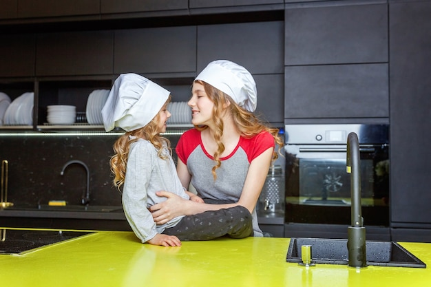 Twee meisjes met koksmuts knuffelen en plezier hebben in de keuken. zusters klein kind en tienermeisje koken gezond voedsel thuis. jeugd, gezin, huishouden, teamwerk helpen concept